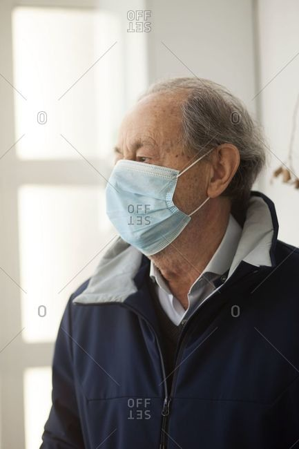 Elderly man putting on a protective face mask before going out