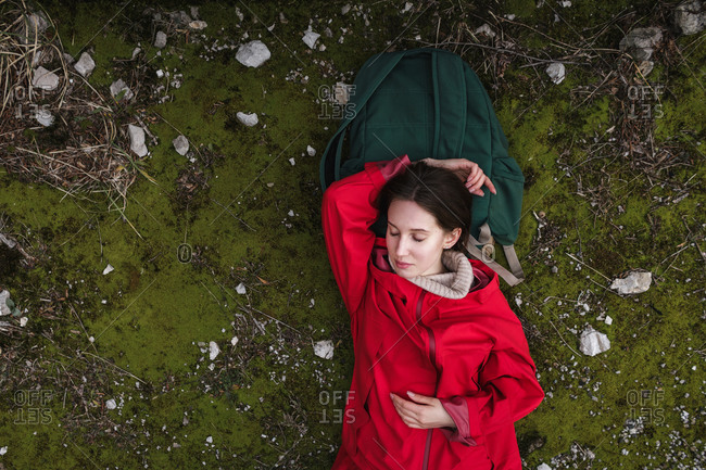 The girl lies on the green moss and looks up