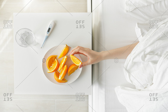 The hand reaches for the oranges in the white plate on the nightstand