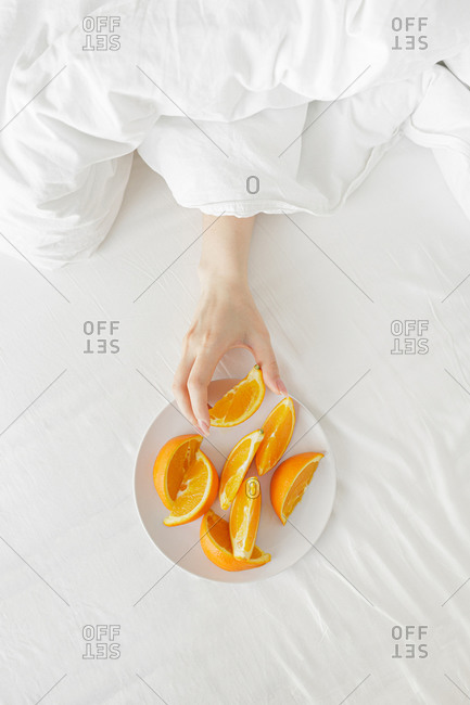 Juicy oranges lie in a white plate on the bed