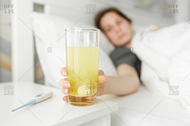 A sick girl reaches for a glass of medicine