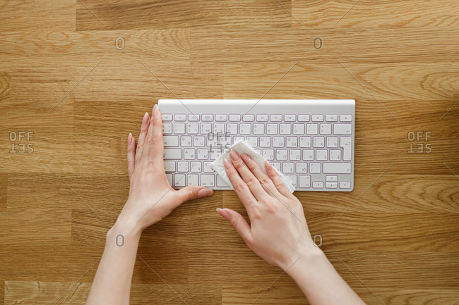 The girl wipes the keyboard with a special tool