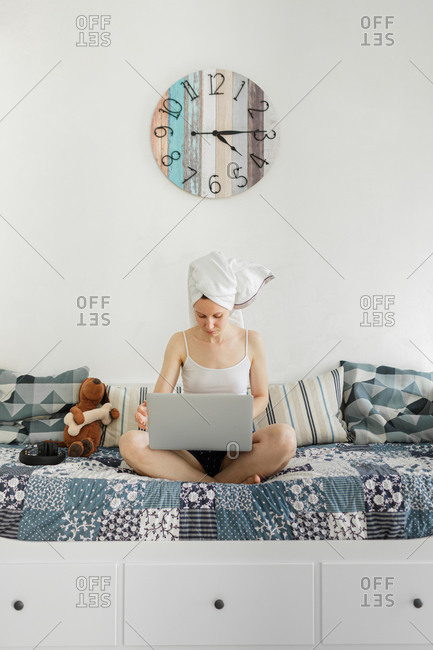 Young woman sitting in her sofa, working from home on laptop
