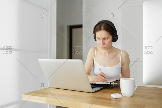 Young woman sitting in her desk, working from home on laptop