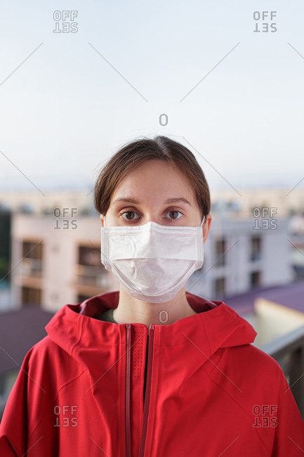 Woman in a medical protective mask against the background of the city
