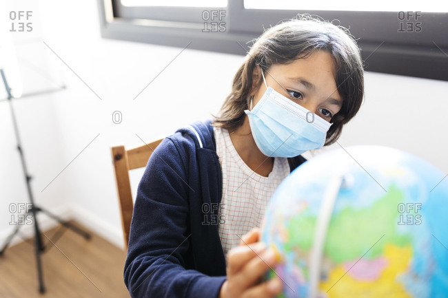 Boy exploring a globe while wearing a medical mask