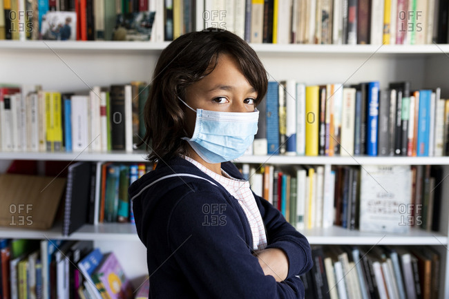 Portrait of a tweenager in medical mask at home