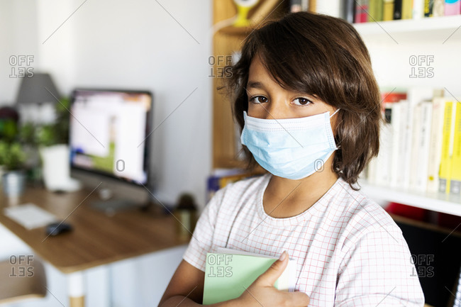 Young boy with asthma wearing medical mask at home