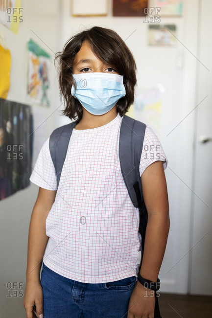 Young student in mask preparing for school
