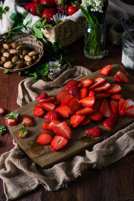 Sliced strawberries on cutting board for preparing dessert