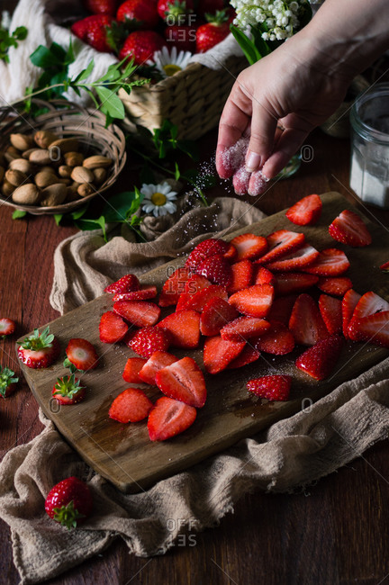 Young woman sprinkling vanilla sugar over sliced strawberries for making galette