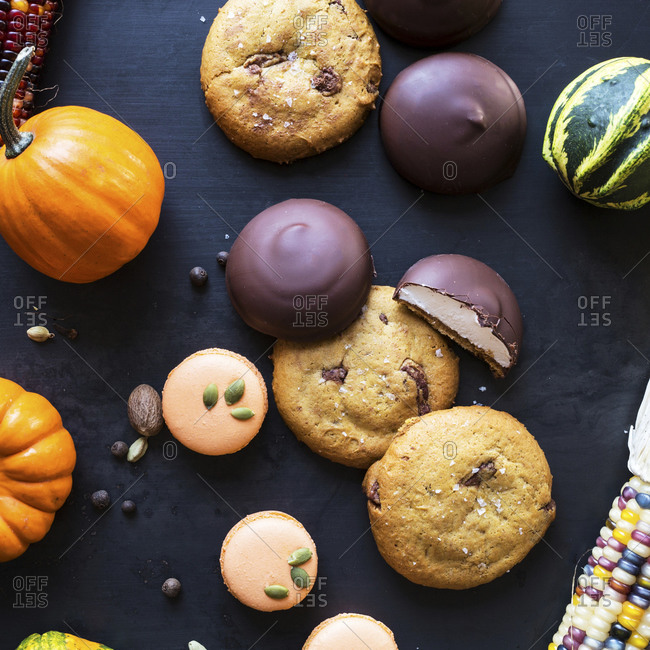 Cookies and gourds on dark surface