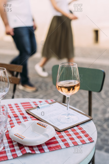 Cannes, France - April 27, 2018: Class of wine on outdoor table at an Italian restaurant in the old town of Cannes