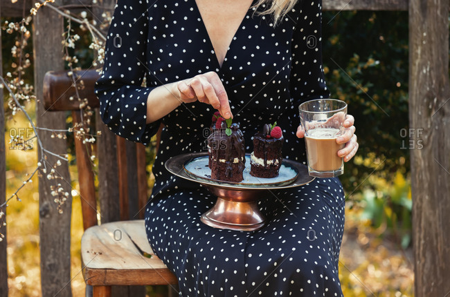 Woman sitting in chair with glass of coffee and chocolate cake