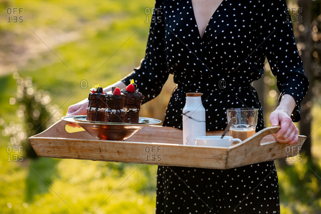 Female hold tray with chocolate cake and coffee on backyard in sunset time