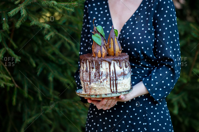 Woman holds pear cake with chocolate near a spruce tree at outdoor