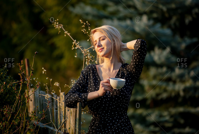 Beautiful blonde woman with cup of coffee at countryside outdoor in sunset time