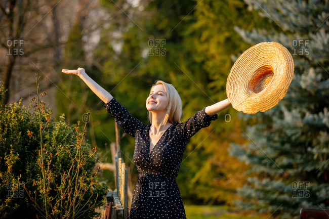 Beautiful blonde woman in hat at countryside outdoor in sunset time