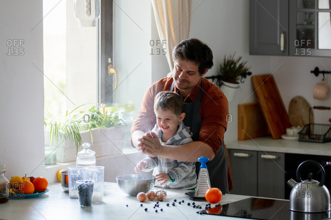 Dad and son have fun cooking in the kitchen