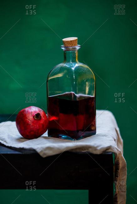 Garnet syrup in a bottle and fruit on green background
