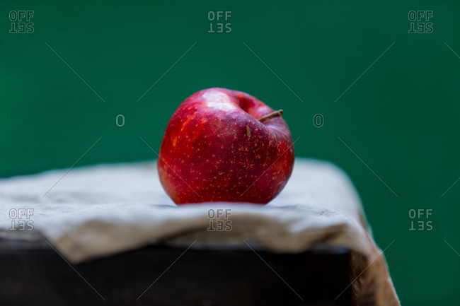 Red apple on napkin on green background
