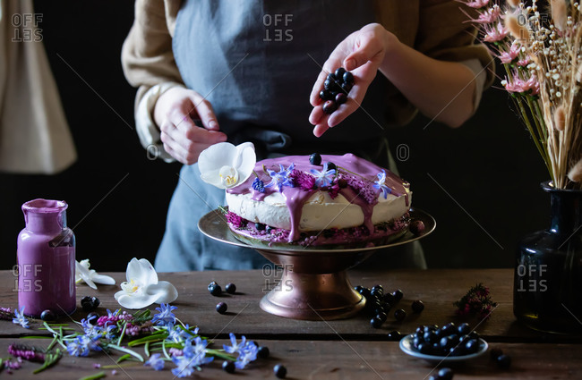 Woman decorating a meringue pie with blueberry in the kitchen at home