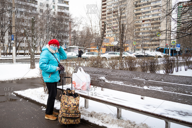 Moscow, Russia - March 31, 2020: Lady leaves supermarket loaded with shopping and wearing mask as preventive measure against the outbreak of the coronavirus