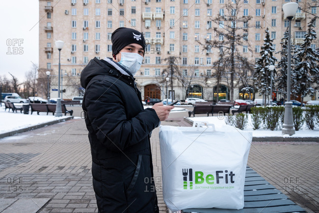 Moscow, Russia - March 31, 2020: Food delivery person works using a protective mask against the coronavirus