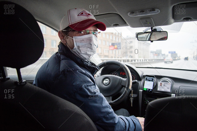 Moscow, Russia - March 31, 2020: Taxi driver drives wearing protective mask prescribed for the category against the new coronavirus