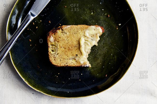 Half eaten slice of banana bread with butter