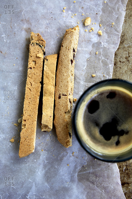 Freshly baked biscotti on wax paper and baking tray with black coffee