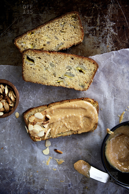 Sliced banana bread with peanut butter and almond flakes on a rustic background