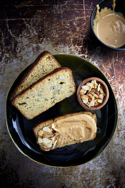 Sliced banana bread with peanut butter and almond flakes on a green plate & rustic background