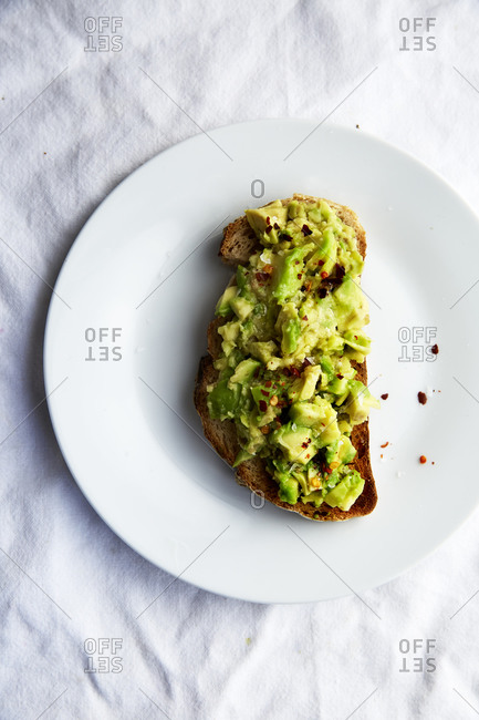 Avocado Toast with chilli flakes on a white plate on white linen