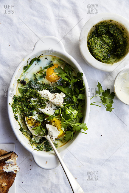 Eggs baked in spinach herbs and green pesto on a white linen countertop