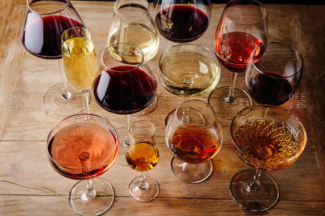 Elevated view of various wines and cocktails served in glasses on a wooden table