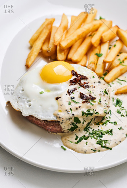 Hamburger with an egg and French fries served in a restaurant