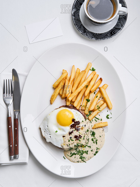 Overhead view of a hamburger with an egg and French fries served in a restaurant