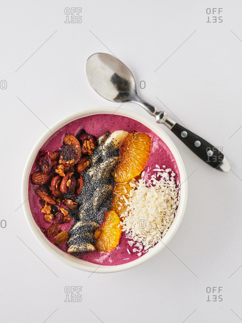 Berry smoothie bowl with fruit, nuts and poppy seeds