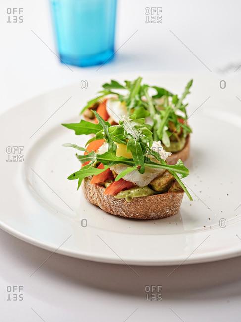 Bruschetta dish with egg, tomato, arugula and avocado