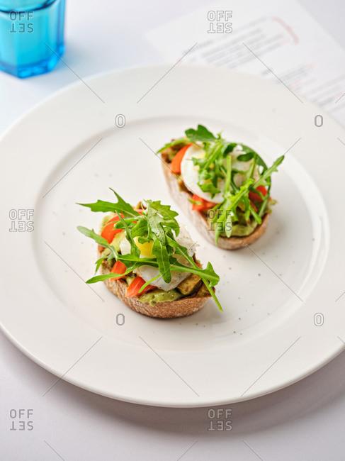 Overhead view of a bruschetta dish with egg, tomato, arugula and avocado