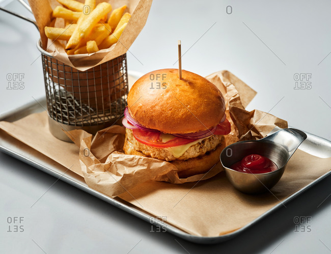 Turkey burger with French fries on a metal tray