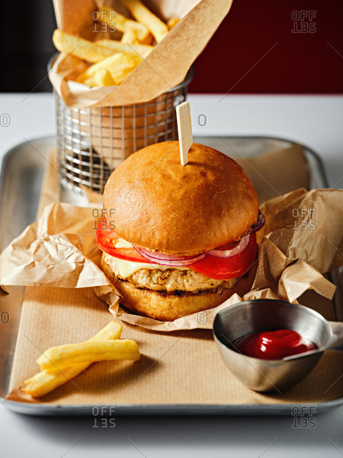 A turkey burger with French fries on a metal tray
