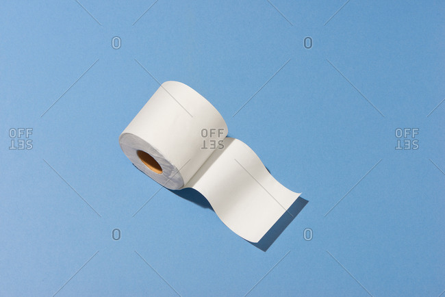 One roll of toilet paper on blue background, top view