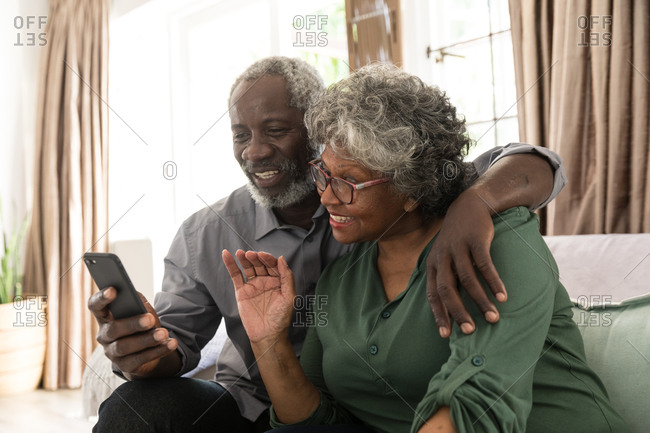A senior African American couple spending time at home together, social distancing and self isolation in quarantine lockdown during coronavirus covid 19 epidemic, the man holding a smartphone and taking a selfie, making a video call to friends or relatives, waving