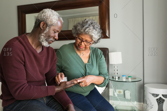A senior African American couple spending time at home together, social distancing and self isolation in quarantine lockdown during coronavirus covid 19 epidemic, the woman pouring tablets from a bottle into hand of the man