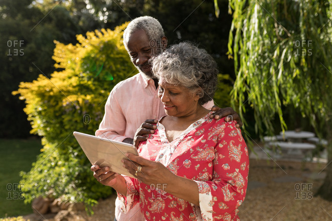 A senior African American couple spending time in their garden together, social distancing and self isolation in quarantine lockdown during coronavirus covid 19 epidemic, using a tablet computer