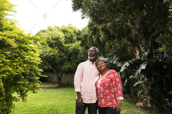 A senior African American couple spending time in their garden together, social distancing and self isolation in quarantine lockdown during coronavirus covid 19 epidemic, embracing and looking away