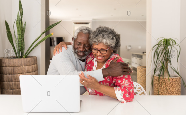 A senior African American couple spending time at home together, social distancing and self isolation in quarantine lockdown during coronavirus covid 19 epidemic, sitting at a table, using a laptop, embracing and smiling