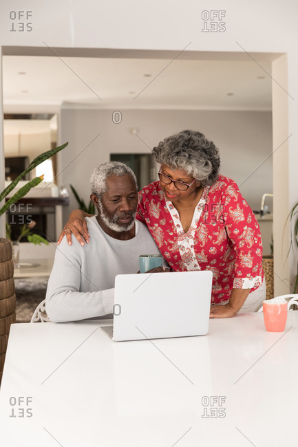 A senior African American couple spending time at home together, social distancing and self isolation in quarantine lockdown during coronavirus covid 19 epidemic, sitting at a table, using a laptop, embracing
